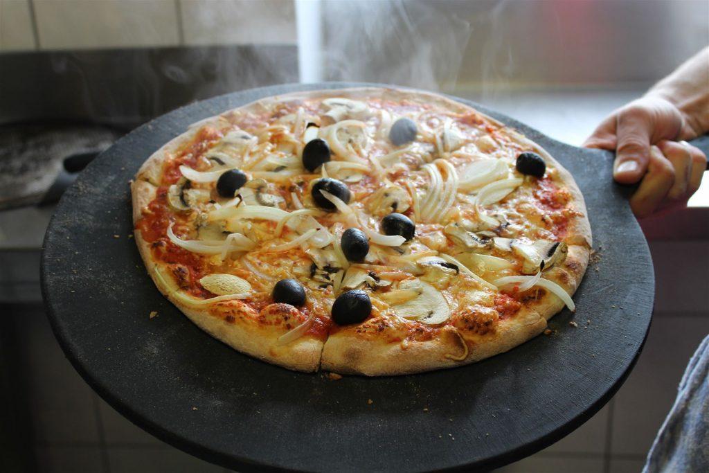 Pizza mit Zwiebeln, Oliven und Tomaten, Käse, Champignons.